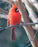 This is a photo of a red bird facing right on a tree branch