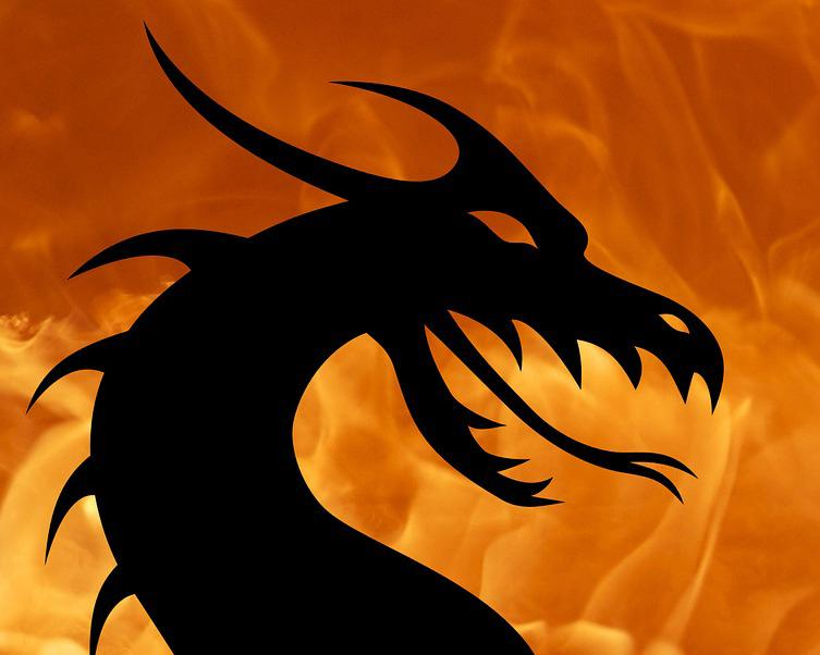 This is a photo of a drawing of a silhouette of dragon with fire in the background