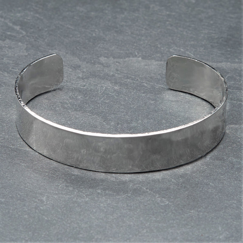 An adjustable, hammered dimpled textured silver simple cuff bracelet designed by OMishka.