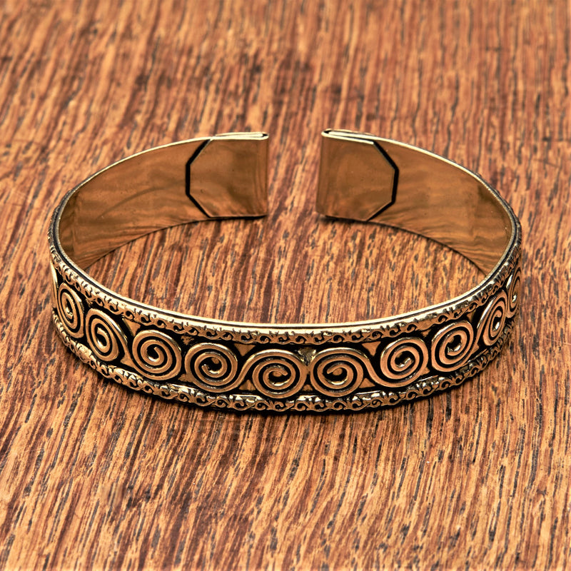 An adjustable, handmade pure brass spiral patterned cuff bracelet designed by OMishka.