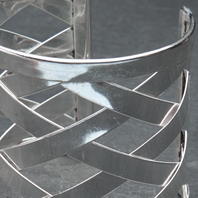 An adjustable, open lattice weave detailed silver wide cuff bracelet designed by OMishka.