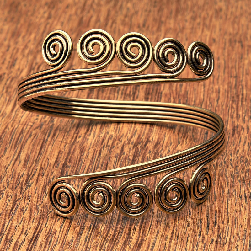 An adjustable, open spiral pure brass arm cuff bracelet designed by OMishka.