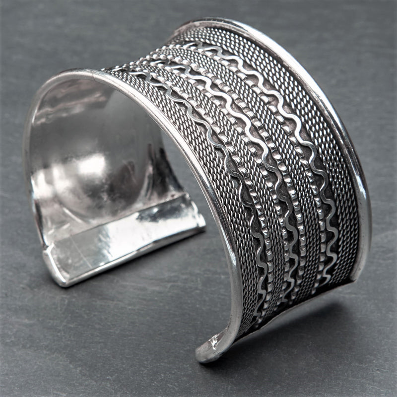 An adjustable, wide concave shaped silver wavy patterned cuff bracelet designed by OMishka.