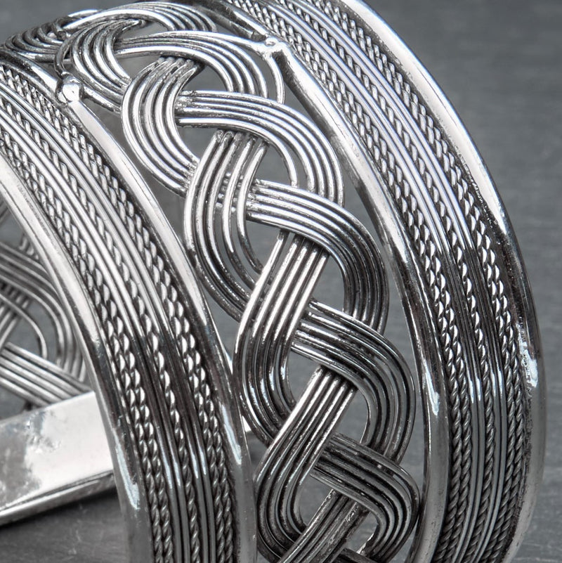 An adjustable. wide woven patterned silver open cuff bracelet designed by OMishka.