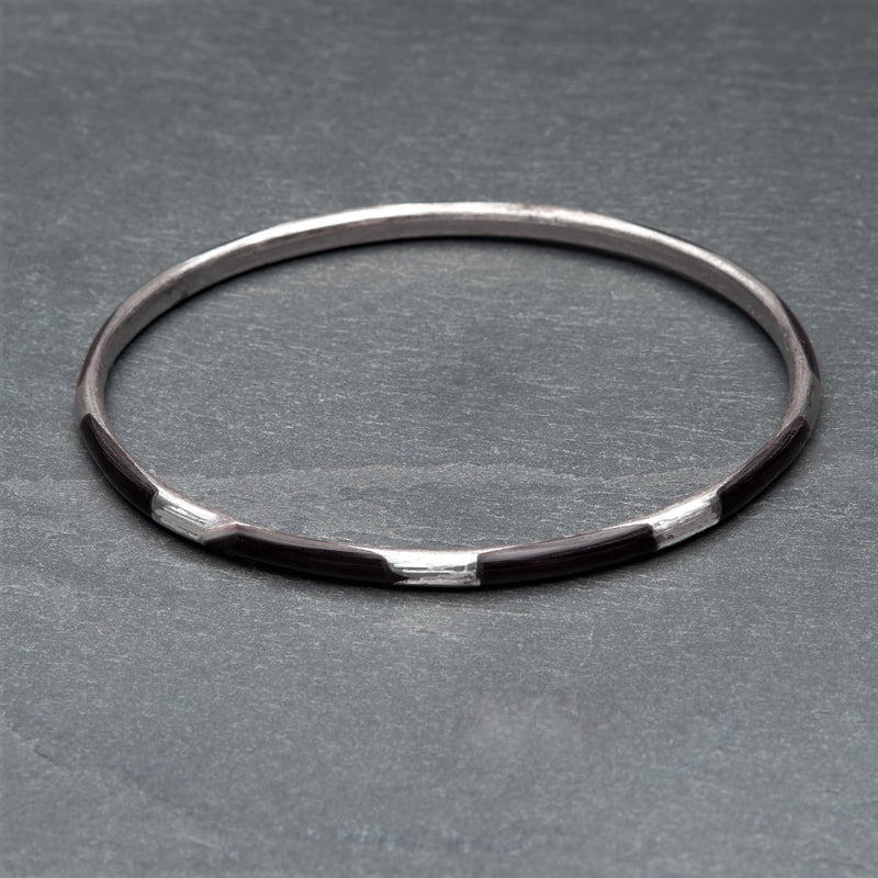 An artisan handmade, silver and black enamel striped thin bangle bracelet designed by OMishka.