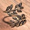 An adjustable, artisan handmade pure brass olive branch wrap ring designed by OMishka.