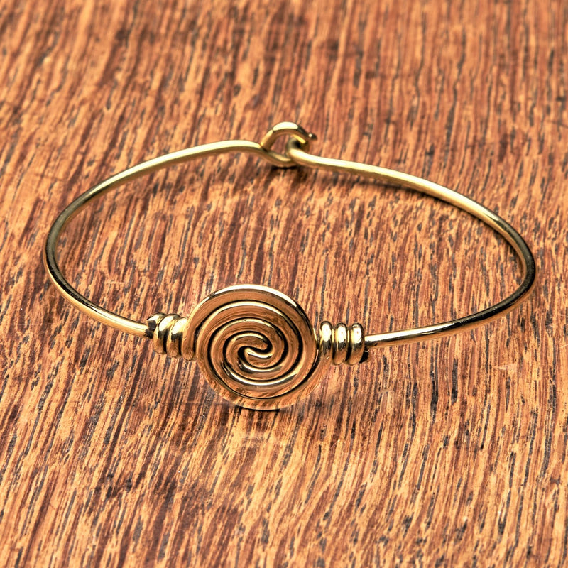 An artisan handmade, pure brass spiral patterned bangle bracelet designed by OMishka.