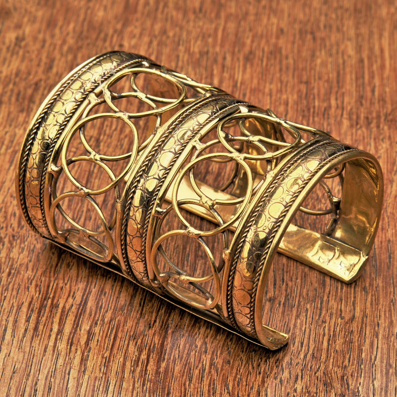An artisan handmade extra wide, pure brass, open circle patterned cuff bracelet designed by OMishka.