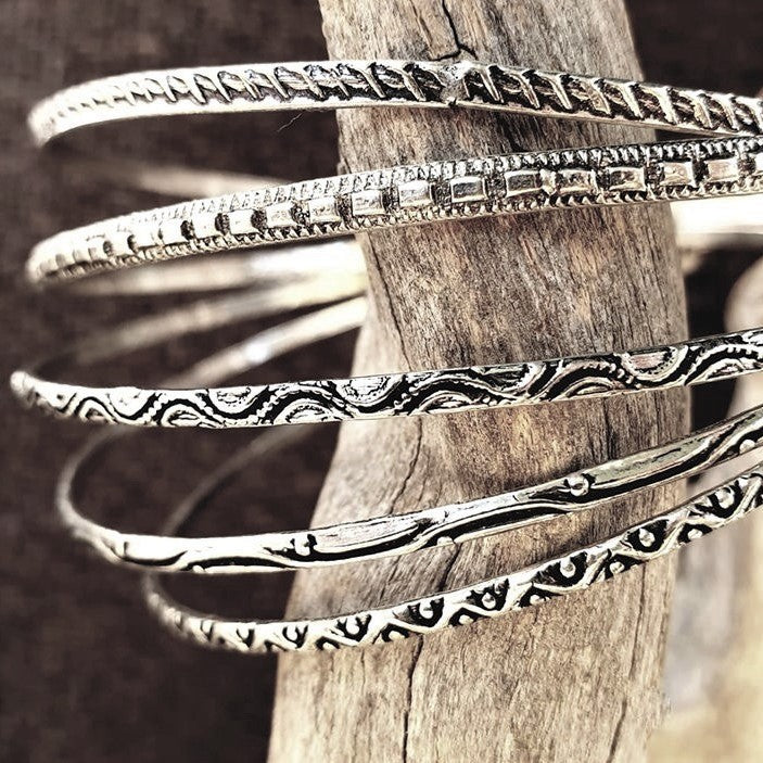 An artisan handmade, silver set of 5 bangle bracelets each etched with traditional Indian patterns designed by OMishka.