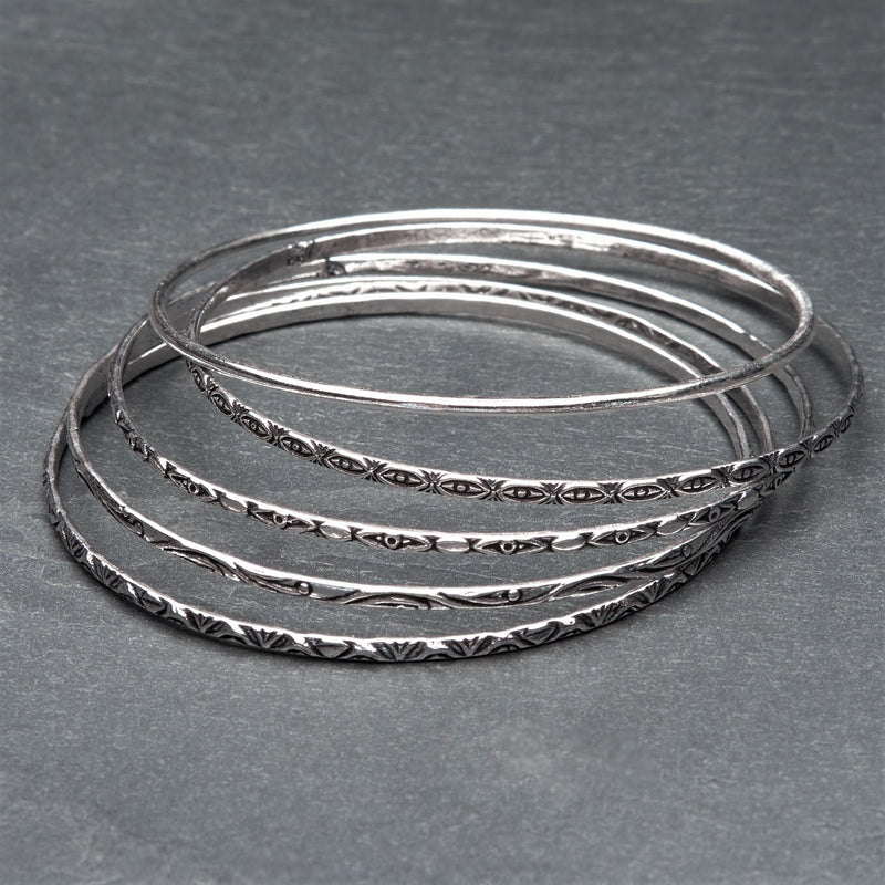 An artisan handmade, silver set of 5 thin bangles each etched with traditional Indian patterns designed by OMishka.