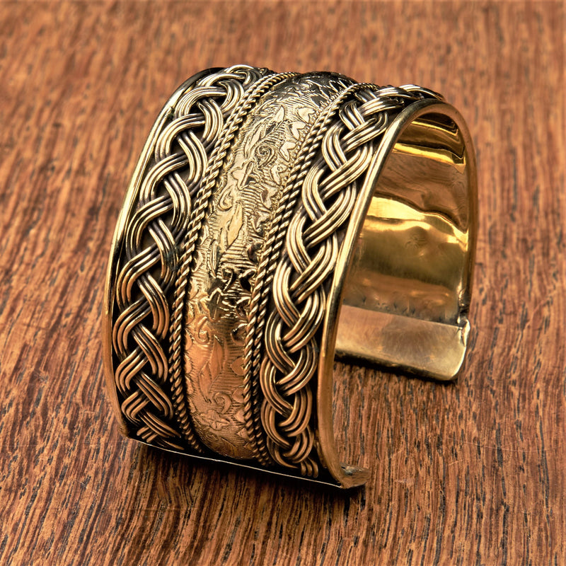 An artisan handmade, wide woven pure brass patterned cuff bracelet designed by OMishka.