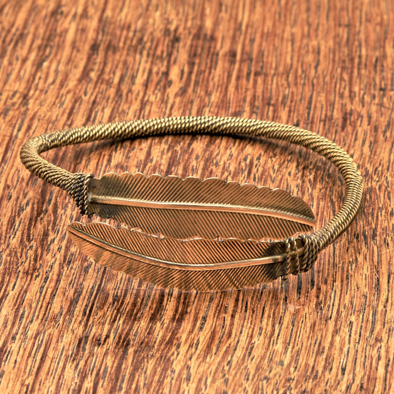 A double feather, pure brass wrap bracelet designed by OMishka.