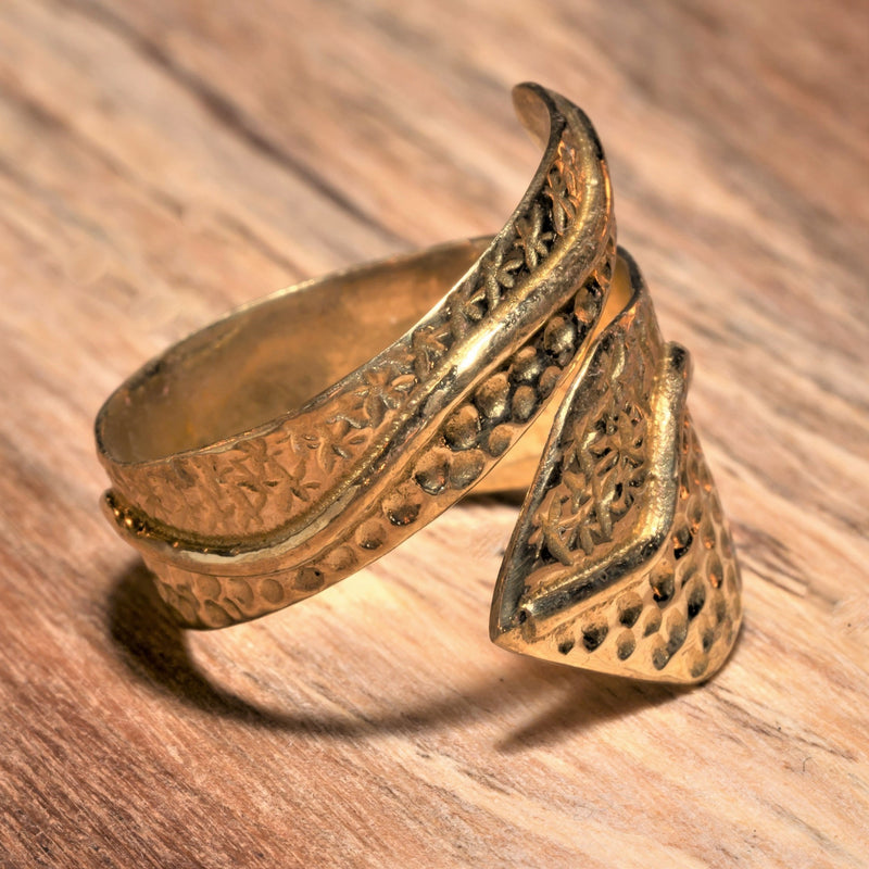 An adjustable, chunky, handmade pure brass, dotted, star and swirl patterned wrap ring designed by OMishka.