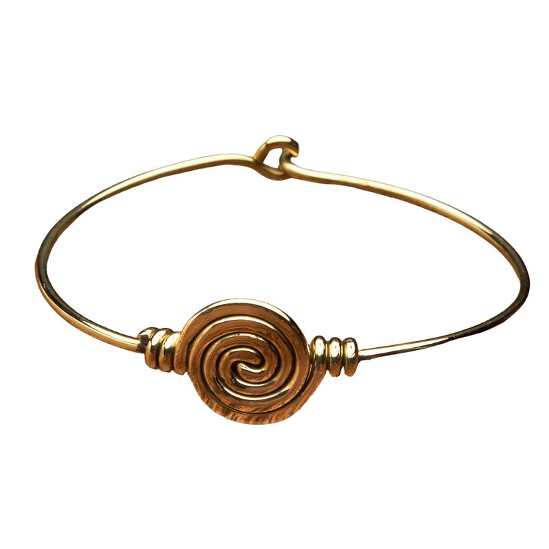 A handmade pure brass spiral patterned bangle designed by OMishka.