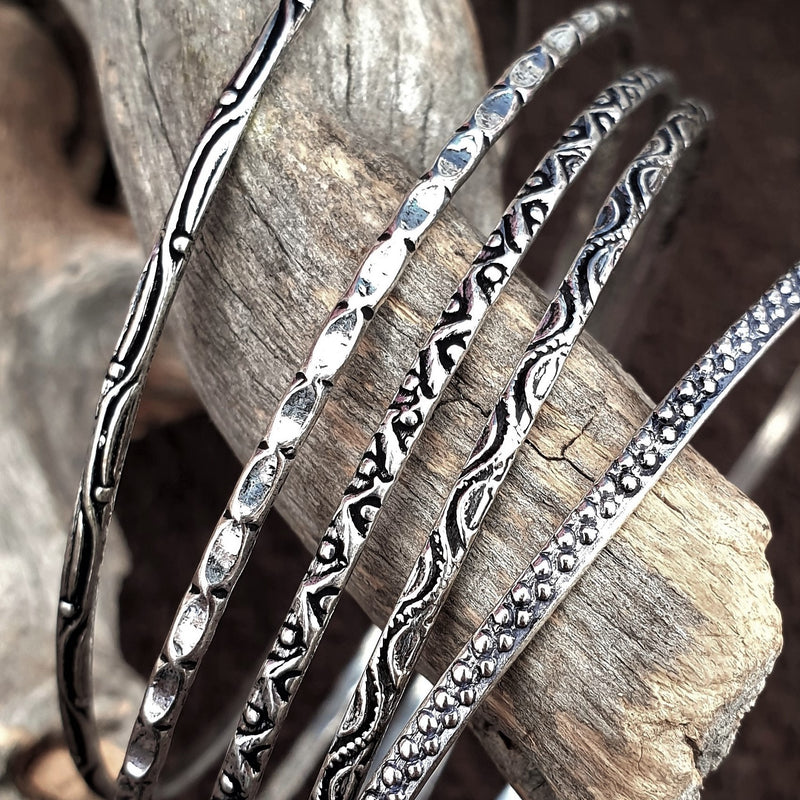 A handmade, silver set of 5 thin bangle bracelets each etched with traditional Indian patterns designed by OMishka.