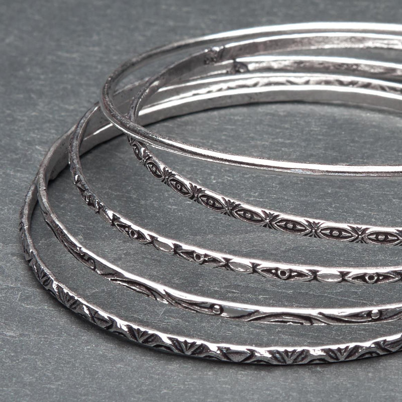 An artisan handmade, silver set of 5 bangles each etched with traditional Indian patterns designed by OMishka.