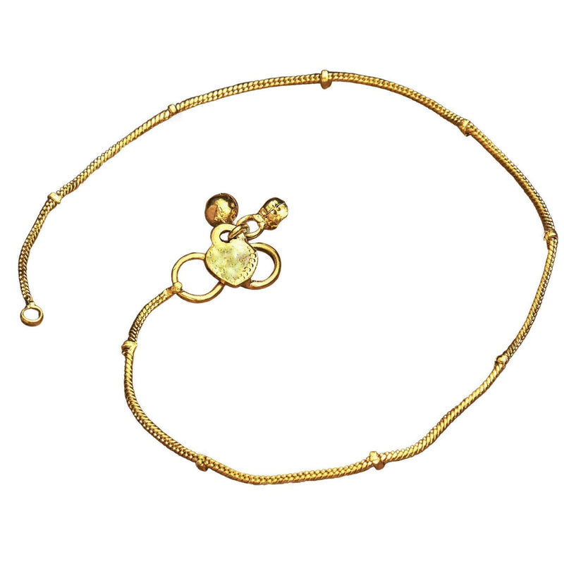 A delicate, pure brass, thin ribbed snake chain ankle bracelet with tiny bells designed by OMishka.