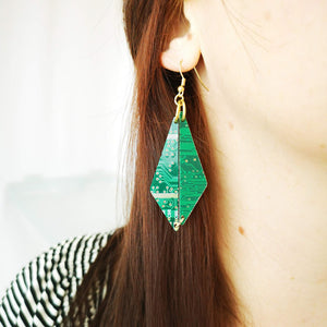 TechWears Green Drop Earrings hanging from a ladies ear. From a gold dangle ear wire, Two bottom heavy diamonds dangle from gold jump rings. They connect at the bottom to give a diamond Drop feel. The Circuit board is dark green with lighter green and gold circuits running though it.