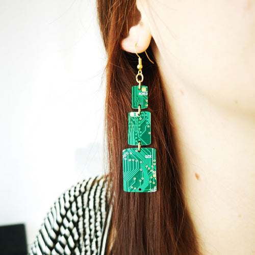 TechWears Green Rectangle Drop Earrings hanging from a ladies ear. From a gold dangle ear wire, a small closed rectangle holds a larger middle rectangle by one gold jump ring in the center, followed by a larger rectangle at the bottom held by another single jump wire, giving a pyramid effect. The Circuit board is dark green with lighter green and gold circuits running though it.