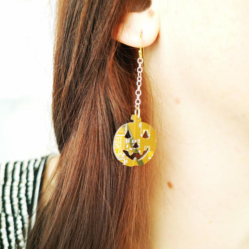 TechWears Green Drop Earrings hanging from a ladies ear. From a gold dangle ear wire a sliver chain holds an orange pumpkin with a smiling Jack-o-lantern face cut out of the circuit board. The Circuit board is light and dark orange with  white and muted yellow circuits running though it.