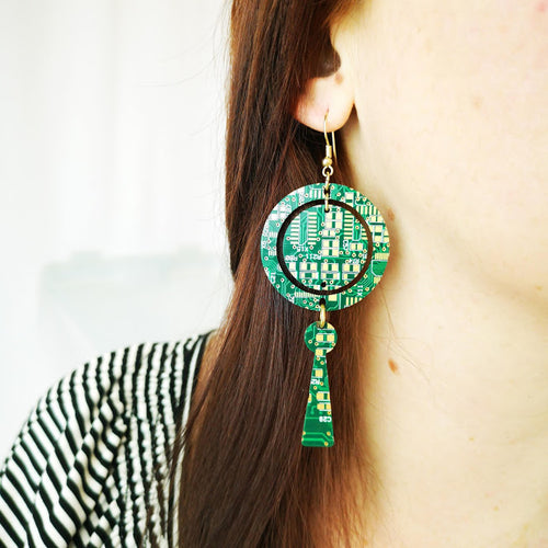 TechWears Green Drop Earrings hanging from a ladies ear. From a gold dangle ear wire, a large open circle holds a smaller closed circle in its centre. a key hole hangs from the bottom of the large open circle. The Circuit board is dark green with lighter green and gold circuits running though it.