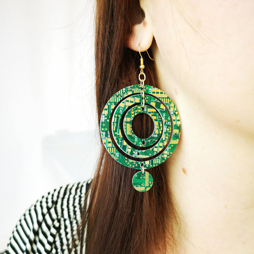 TechWears Green Drop Earrings hanging from a ladies ear. From a gold dangle ear wire, one large open circle encloses a smaller open circle, which encloses a, smaller yet, open circle hanging in its centre. Another small closed circle hangs from the bottom of the largest circle. The Circuit board is dark green with lighter green and gold circuits running though it.