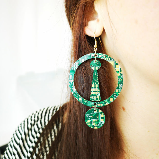 TechWears Green Drop Earrings hanging from a ladies ear. From a gold dangle ear wire, one large open circle encloses a Key hole shape hanging in the centre. A smaller closed circle hangs from the bottom of the large enclosed circle. The Circuit board is dark green with lighter green and gold circuits running though it.