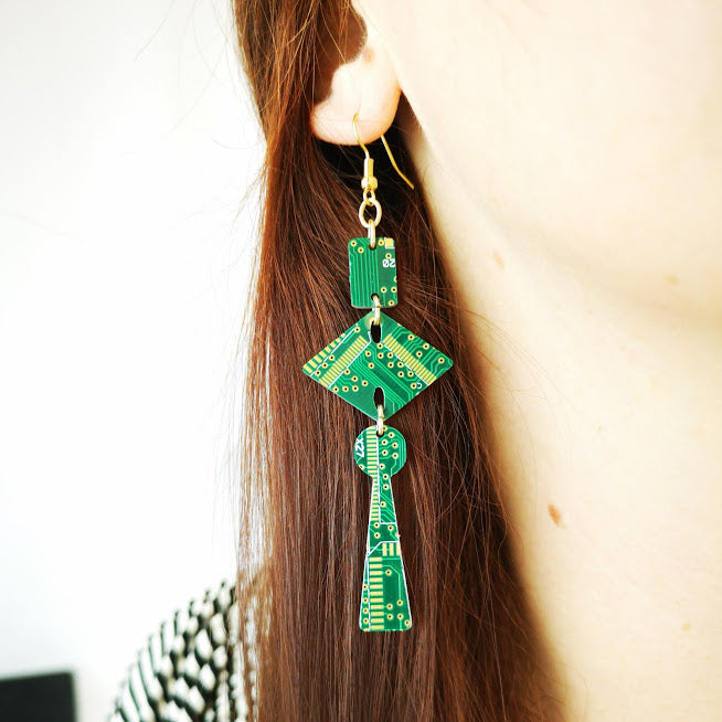 TechWears Circuit Board earrings hang from a ladies ear. From a gold dangle ear wire a small closed rectangle holds a larger diamond shape, which holds a key hole shape at the end. These earrings are long and interesting to look at. The Circuit board is dark green with lighter green and gold circuits running though it.
