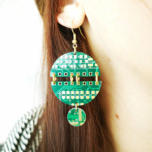 TechWears Green Drop Earrings hanging from a ladies ear. From a gold dangle ear wire, two semicircles are held together by four bold gold jump rings, (One on each end and two in the middle). a small circle dangles from the bottom giving it a planet and moon feel. The Circuit board is dark green with lighter green and gold circuits running though it.