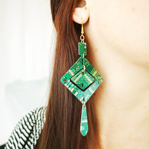 TechWears Green Drop Earrings hanging from a ladies ear. From a gold dangle ear wire, a small rectangle at top drops to a large square diamond enclosing a smaller diamond cut out, from the bottom hangs an elongated tear drop. The Circuit board is dark green with lighter green and gold circuits running though it.