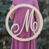 Woman holding wooden monogram circle script letter sign