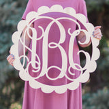An image of a woman holding a pink painted scallop style wooden monogram sign from 48 Hour Monogram.