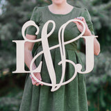 An image of a woman holding a mixed style wooden monogram sign from 48 Hour Monogram.