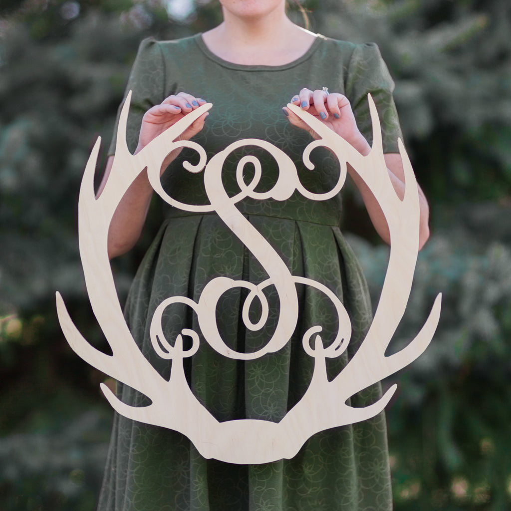 An image of a woman holding the Antler Wooden Monogram Sign from 48 Hour Monogram.