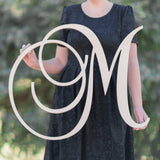 Woman holding one letter monogram sign