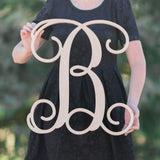 An image of a woman holding a wooden monogram sign in regular font from 48 Hour Monogram.