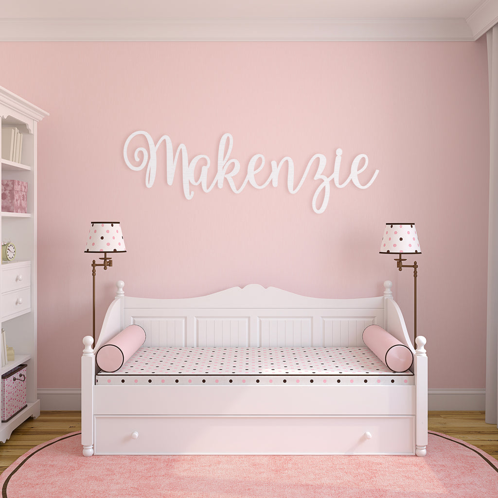 white wooden monogram sign on child's bedroom wall