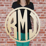 An image of a woman holding the modern style wooden monogram sign from 48 Hour Monogram.