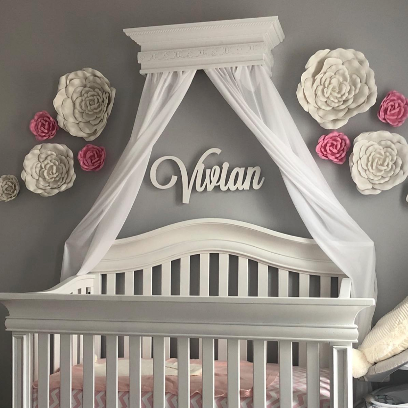 white wooden monogram sign above crib