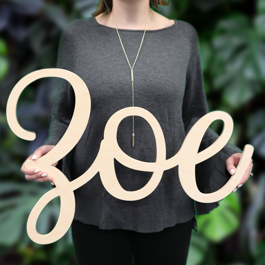An image of a woman holding a wooden monogram sign from 48 Hour Monogram in the Zoe font.