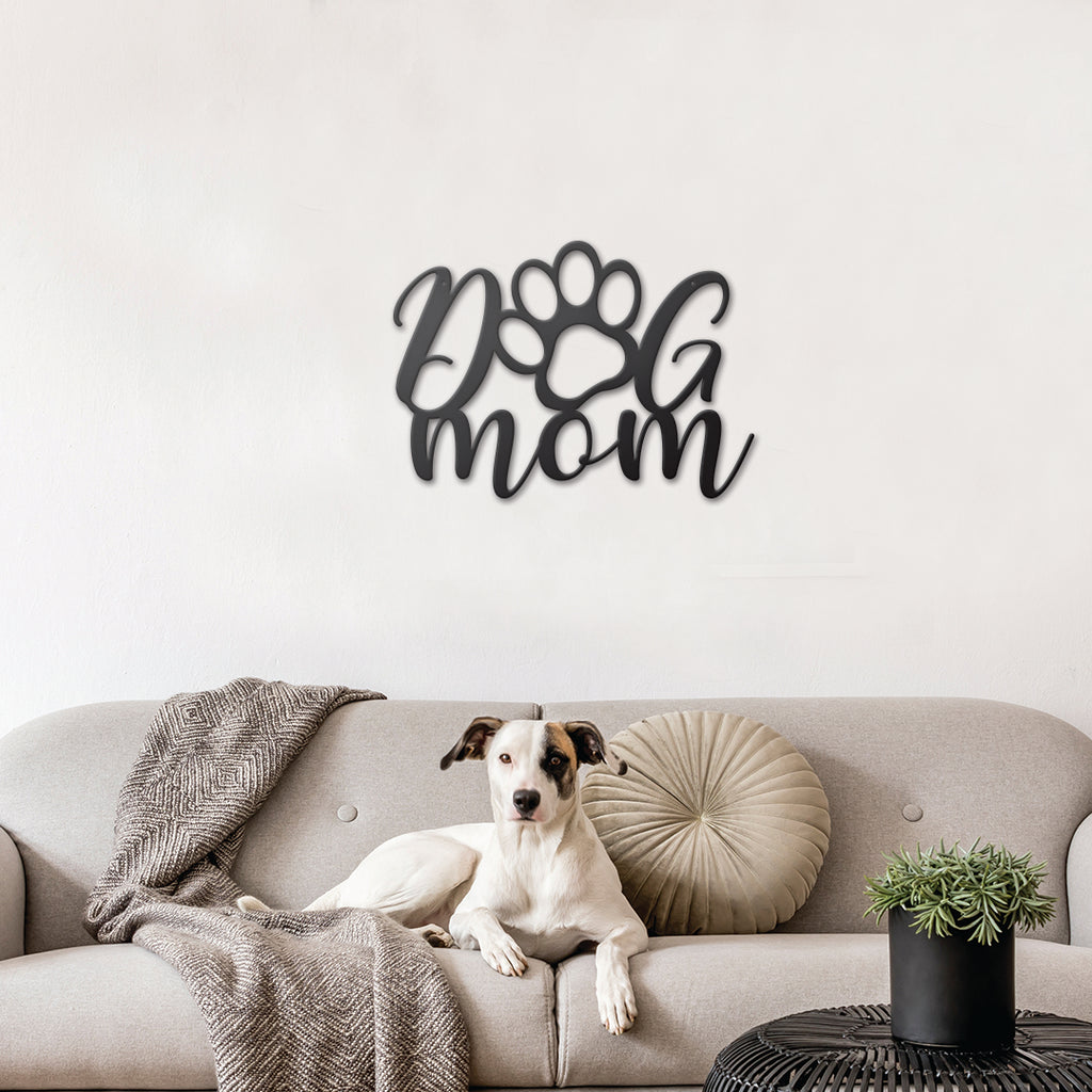 An image of the Dog Mom metal monogram from 48 Hour Monogram hanging behind a couch.