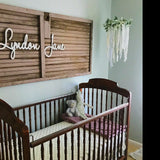 white wooden name sign above crib on nursery wall