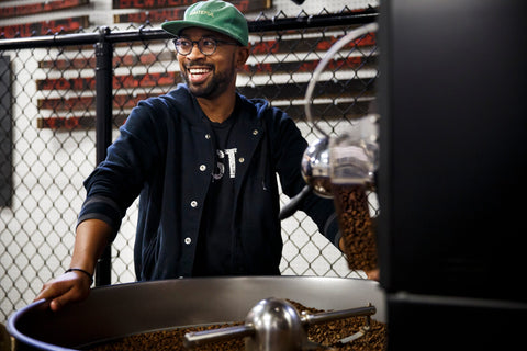 Pernell standing behind a coffee roaster with a jacket and hat on smiling as he looks somewhere off camera