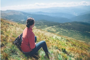 Woman Sitting on the side of a hill looking over a valley and mountains.