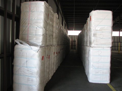Cotton bales stacked and ready for spinning in American warehouse.