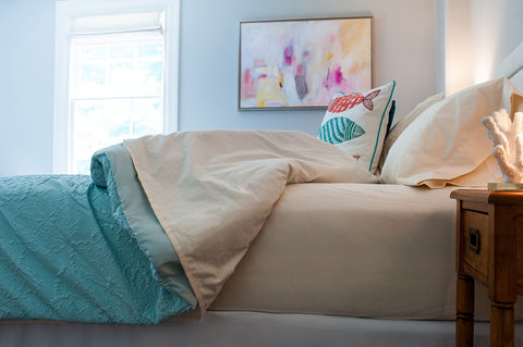 Classic hemmed sheet, unbleached in warm beige, styled with blue blanket.