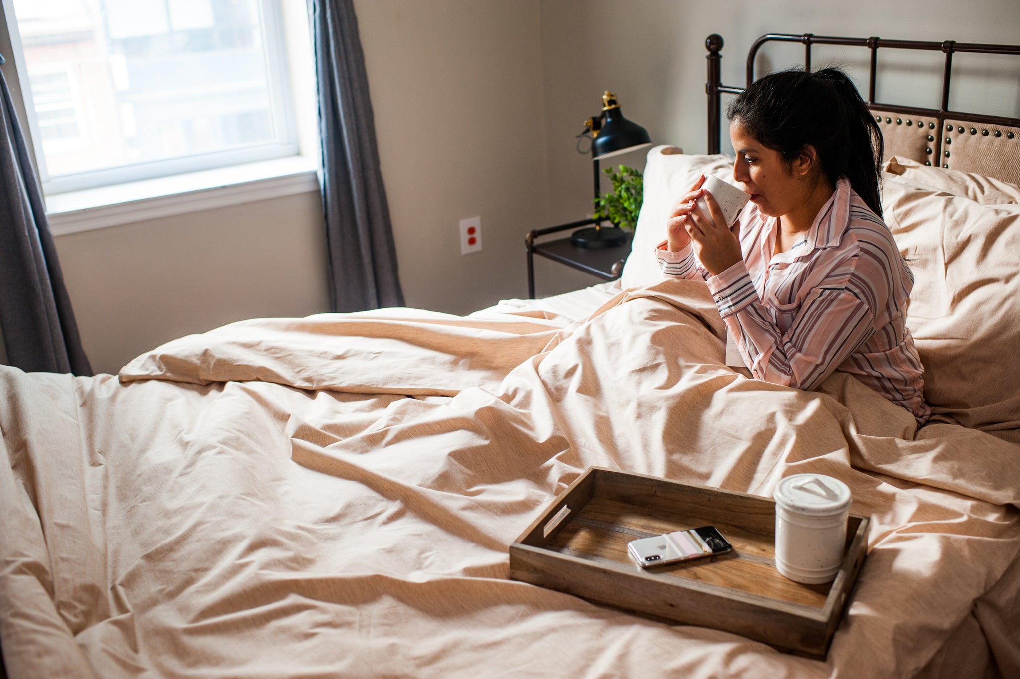 Woman sitting in bed made with Natural organic cotton sheets drinking a hot beverage.