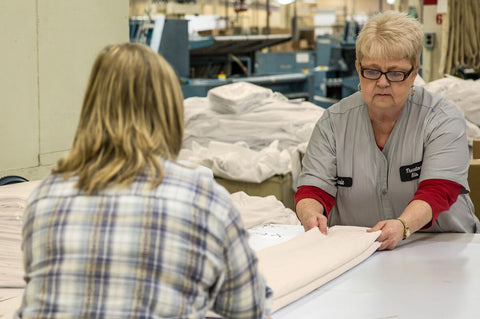 American Blossom Linens textile experts folding classic sheets in Thomaston Georgia factory.
