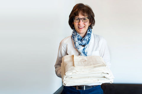 Founder Janet Wischnia holding American favorite all natural classic organic cotton sheets.