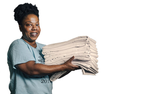 Woman holding pile of classic, unbleached, folded sheets.